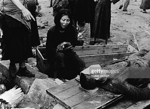 A wounded woman grieves beside the body of an air raid victim following a Japanese attack during the Second SinoJapanese War