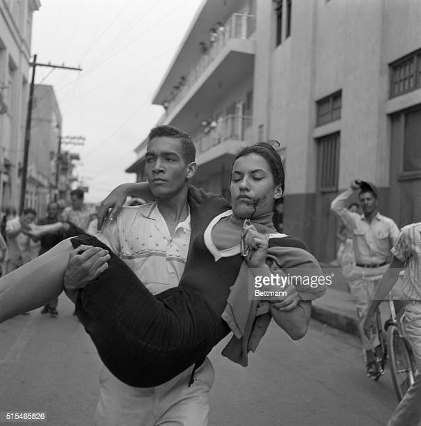 A wounded woman is carried away from scene after a truckload of army troops moved against a crowd of 1000 women demonstrators hurling noise bombs and...