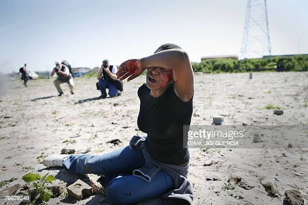 A wounded woman sits on the ground 10 September 2007 after South African riot police firied rubber bullets and stone grenades at hundreds of...
