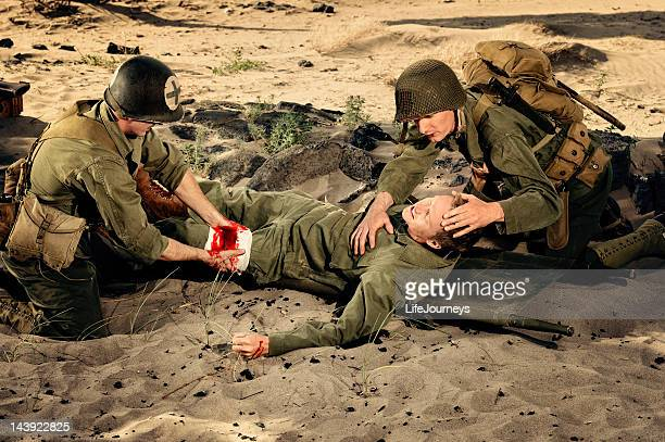 wounded wwii soldier being triaged by medic and commrad - wounded soldier stock photos and pictures