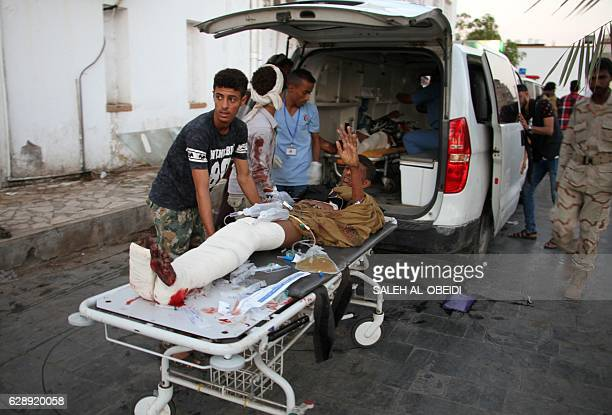 A wounded Yemeni man is taken off an ambulance on December 10 2016 after a suicide bomber killed 35 soldiers and wounded around 50 others at a...