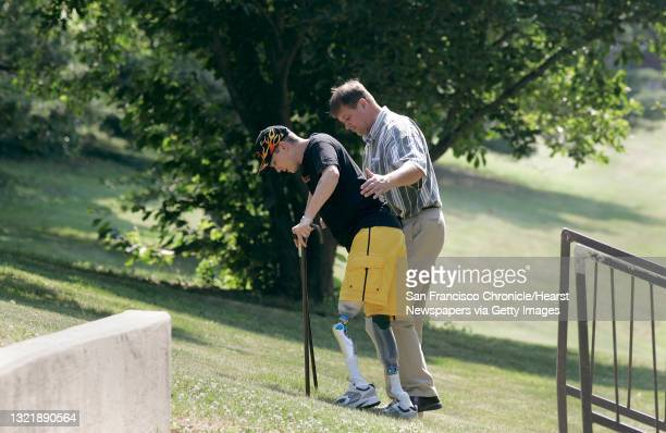 Wounded_087_mac.jpg On the grounds of Walter Reed Army Hospital, Michael works with his physical therapist Robert Bahr, climbing hills in his new...