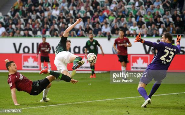 Wout Weghorst of VfL Wolfsbur is challenged by Kevin Wimmer of Hannover 96 as Michael Esser of Hannover 96 attempts to save during the Bundesliga...