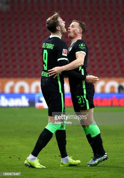 Wout Weghorst of VfL Wolfsburg celebrates with team mate Yannick Gerhardt after scoring their side's first goal during the Bundesliga match between...