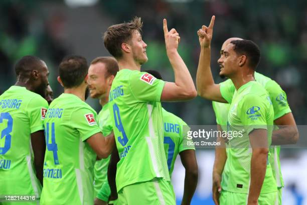 Wout Weghorst of VfL Wolfsburg celebrates with teammates after scoring his team's first goal during the Bundesliga match between VfL Wolfsburg and...