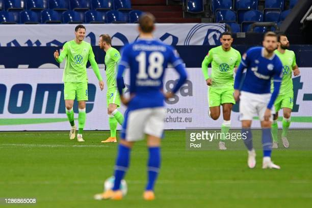 Wout Weghorst of VfL Wolfsburg celebrates with teammates after scoring his team's first goal during the Bundesliga match between FC Schalke 04 and...
