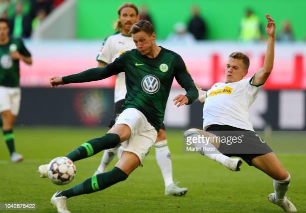 Wout Weghorst of VfL Wolfsburg scores the second equalising goal past Matthias Ginter of Borussia Monchengladbach during the Bundesliga match between...