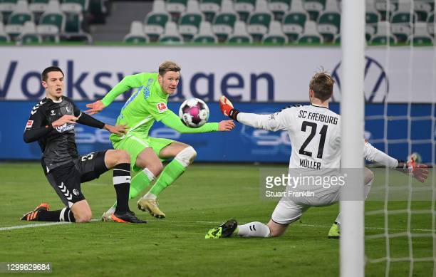 Wout Weghorst of VfL Wolfsburg scores their side's second goal past Florian Muller of Sport-Club Freiburg whilst under pressure from Keven...