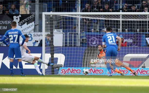 Wout Weghorst of Wolfsburg scores his team's first goal past goalkeeper Oliver Baumann of Hoffenheim by penalty after a hand by Sebastian Rudy of...