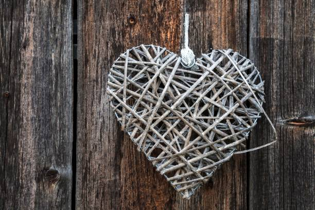 Woven heart hanging on an old wooden facade made of weathered wood, near Oberstdorf, Oberallgaeu, Allgaeu, Bavaria, Germany