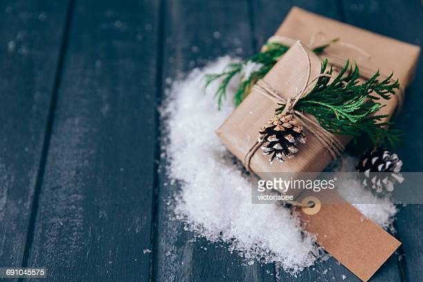 Wrapped Christmas gifts with pine cone, fir and fake snow decoration