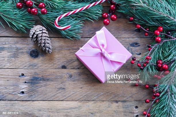 Wrapped christmas present, fir tree branches, mistletoe seed and pine cone on old wooden background. Top view and copy space