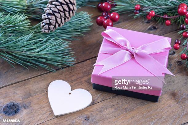 Wrapped christmas present, heart shape, fir tree branches, mistletoe seed and pine cone on old wooden background. Selective focus and copy space