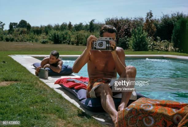 Wrapped in a towel French fashion designer Hubert de Givenchy sits on an outdoor pool deck and looks through the viewfinder of a camera France 1961...