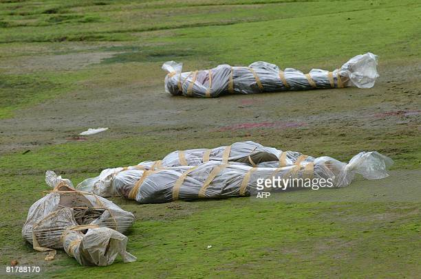 Wrapped in plastic cover the bodies of fourwould be immmigrants are pictured in the yard of Gabosep a coroner office in Libreville on July 01 2008 At...