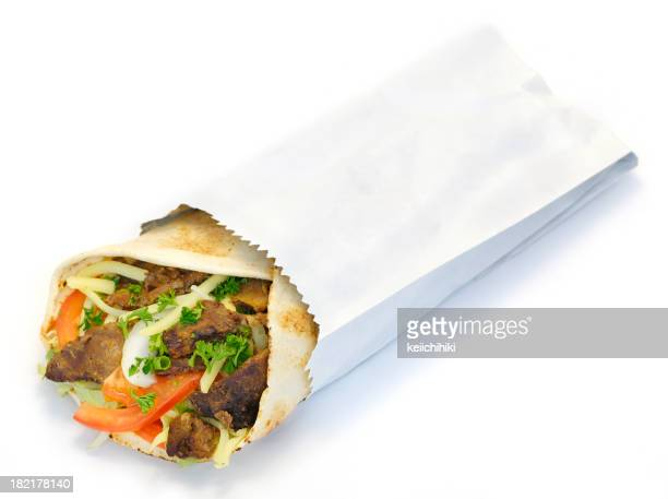 Wrapped kebab served in a white paper bag