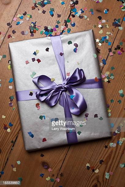 A wrapped present surrounded by confetti