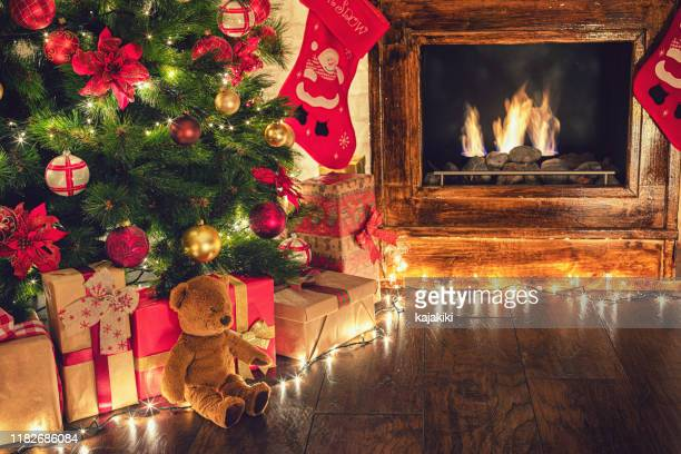 wrapped presents under the christmas tree in a cozy festive atmosphere - living room wallpaper stock pictures, royalty-free photos & images
