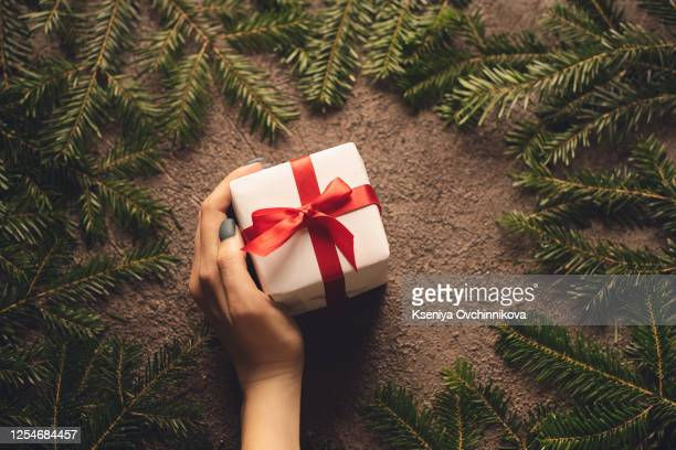 wrapping christmas presents with branches of christmas tree and pine cones. vintage style. - christmas past and christmas present stock pictures, royalty-free photos & images