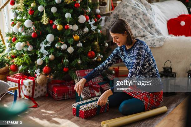 Wrapping gifts under Christmas tree