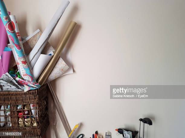 wrapping papers in basket on table against wall at home - sabine kriesch stock-fotos und bilder