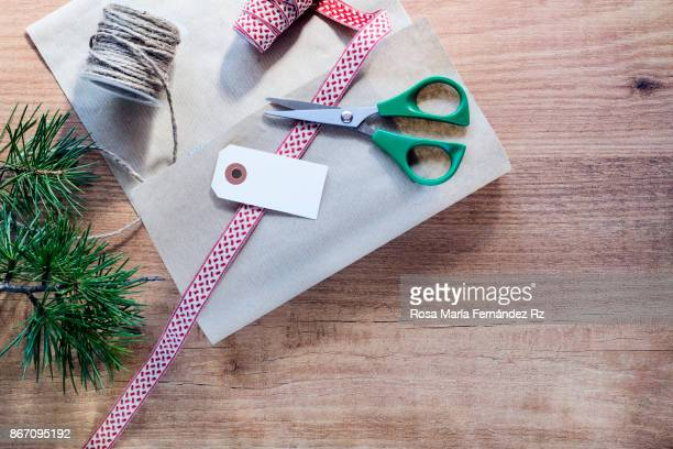 Wrapping procces of Christmas gifts on abstracts wooden background. Top view and copy space.