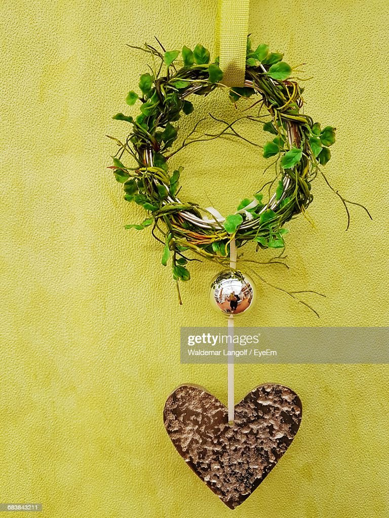 Wreath And Heart Shape Decoration Hanging Against Yellow Wall Stock ...