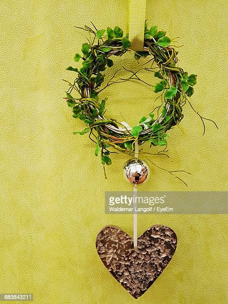 Wreath And Heart Shape Decoration Hanging Against Yellow Wall