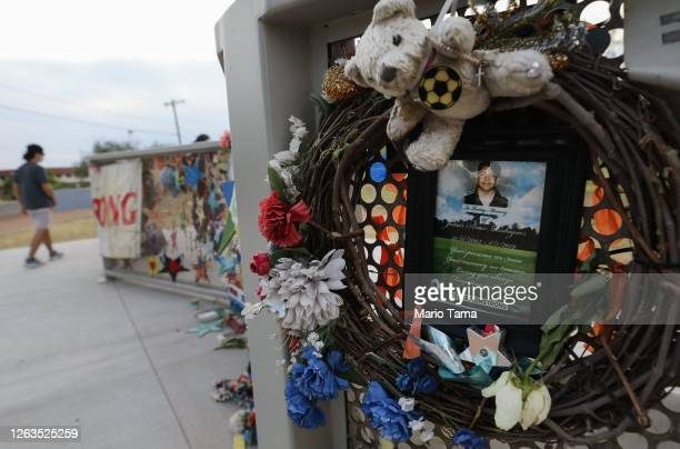 Wreath and photo honors 15-year-old victim Javier Amir Rodriguez at a temporary memorial in Ponder Park honoring victims of the Walmart shooting...