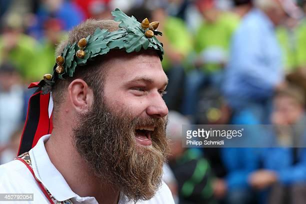 Wreath crowned Swiss Alpine wrestler Benji von Ah smiles after the Alpine Wrestling Festival BruenigSchwinget at the top of the Bruenig Pass on July...