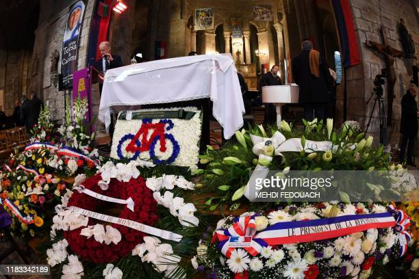 TOPSHOT Wreath flowers of French President and Prince of Monaco lay on the ground as people attend the funerals of French cyclist Raymond Poulidor in...