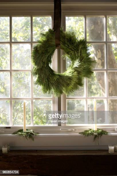 Wreath hanging against window at home