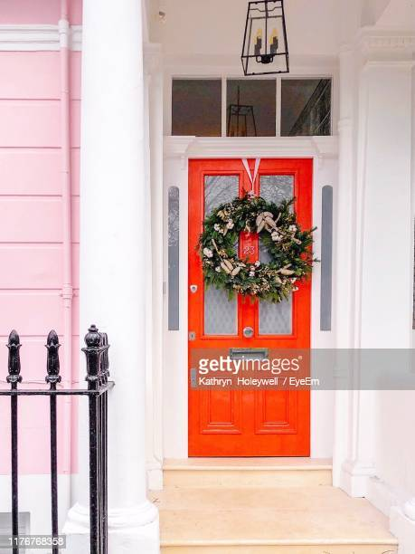 wreath hanging on closed door of building - wreath stock pictures, royalty-free photos & images
