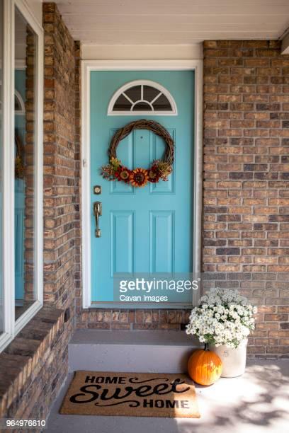wreath hanging on door with pumpkin in front of house during halloween - front door stock pictures, royalty-free photos & images