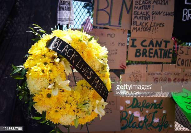 A wreath is seen in front of messages on the security fence on the north side of Lafayette Square near the White House in Washington DC on June 8...