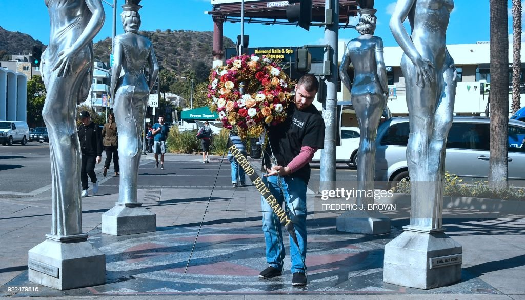 A wreath of flowers arrives, courtesy of the Hollywood Chamber of Commerce, in tribute to the late Evangelist Pastor Billy Graham in Hollywood, California, on February 21, 2018. Graham, the influential Southern preacher who became a spiritual advisor to several US presidents and millions of Americans via their television sets, died Wednesday. He was 99. / AFP PHOTO / Frederic J. BROWN