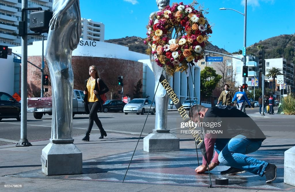 A wreath of flowers is tied down, courtesy of the Hollywood Chamber of Commerce, in tribute to the late Evangelist Pastor Billy Graham in Hollywood, California on February 21, 2018. Graham, the influential Southern preacher who became a spiritual advisor to several US presidents and millions of Americans via their television sets, died Wednesday. He was 99. / AFP PHOTO / Frederic J. BROWN