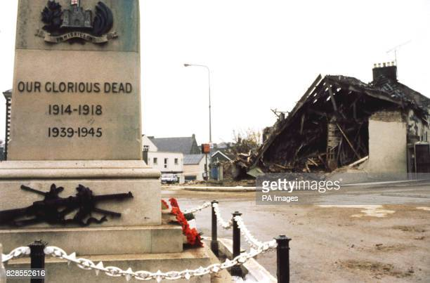 A wreath of poppies lies on the Cenotaph at Enniskillen with the devastated community centre in the background
