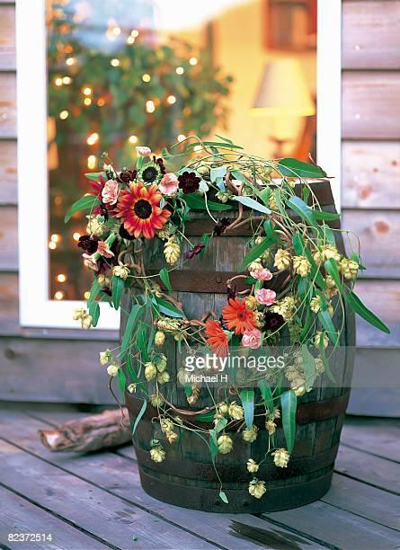 Wreath of vine,hop,gerbera and cosmos on barrel.