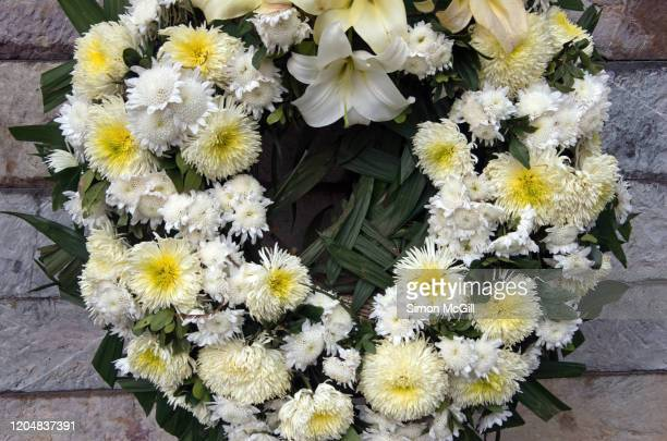 wreath of white flowers against a stone wall - funeral stock pictures, royalty-free photos & images