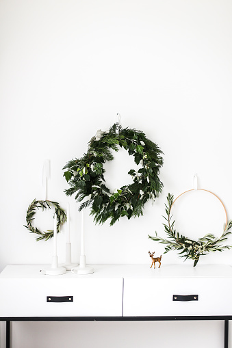 Wreaths hanging on a wall by a sideboard - gettyimageskorea