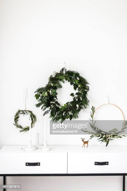 Wreaths hanging on a wall by a sideboard