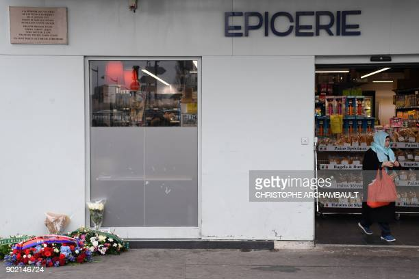 Wreaths have been placed under a commemorative plaque as a woman leaves the Hypercacher market in Porte de Vincenne in eastern Paris on January 7...
