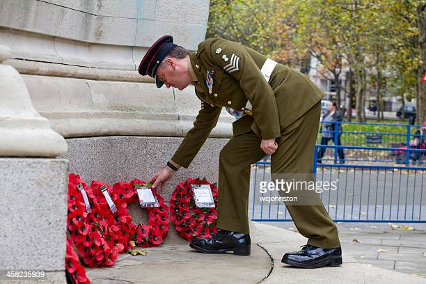 wreaths layed at the war memorial, euston railway station - remembrance sunday stock photos and pictures