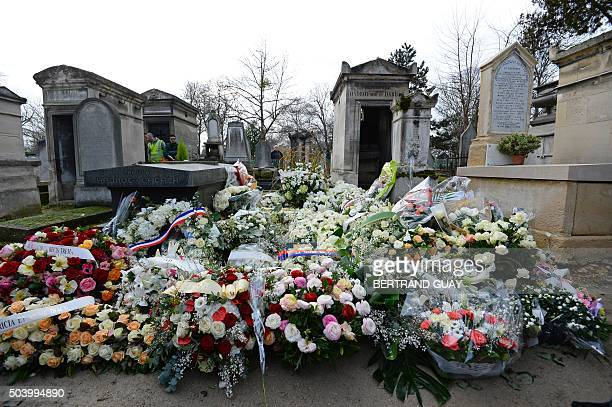 Wreaths of flowers cover the gravestone of late French singer Michel Delpech during his burial ceremony on January 8 2016 at the PereLachaise...
