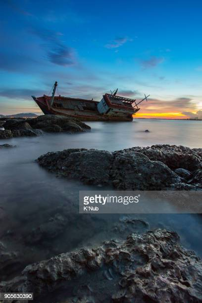 wreck fishing boat on rock beach at sunset time