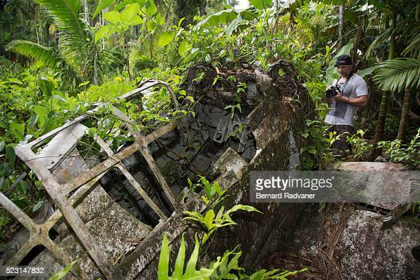 wreck of a zero fighter plane with a tourist in the jungle on peluliu island, palau - mitsubishi a6m zero stock photos and pictures
