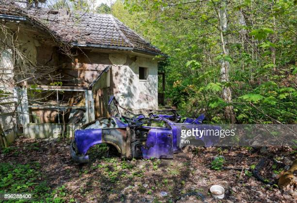 wreck of an old ddr-car near a ruined abandoned house (usedom, germany) - junkyard stock photos and pictures
