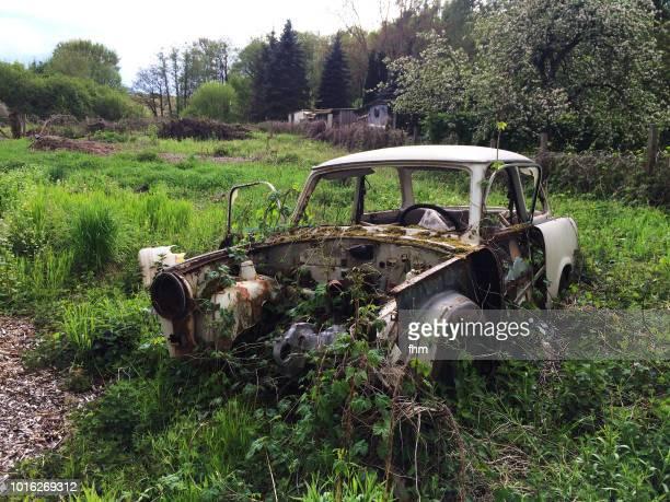 wreck of an old ddr-car on a lawn - alemania del este fotografías e imágenes de stock