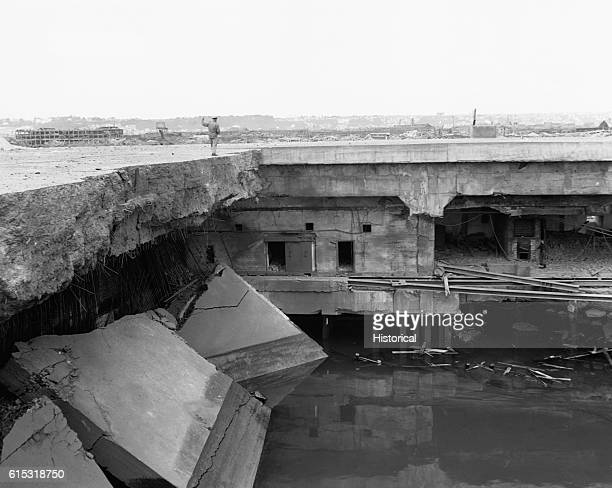 Wreckage at Le Havre France following Allied aerial bombing and naval shelling A US Navy officer walks along the top of the remains of a German...